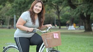 exercícios aeróbicos para emagrecer - mulher asiática um pouco gordinha andando de bicicleta