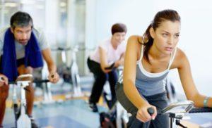 exercícios aeróbicos para emagrecer - 2 mulheres e 1 homem pedalando em bicicletas ergométricas com expressões de desanimo