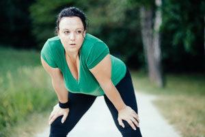 exercícios aeróbicos para emagrecer - foto de uma mulher cansada depois de uma corrida no parque
